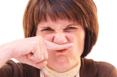 鼻を指で押さえる中年女性