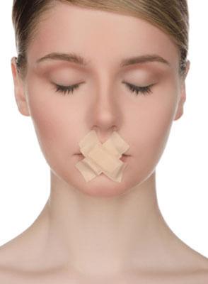 口にテープを貼る女性