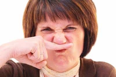臭いと鼻を押さえる中年女性