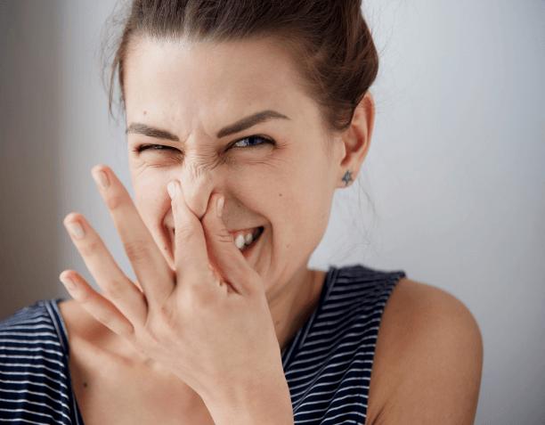 臭い臭いと鼻をつまむ女性